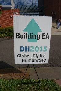 Sign saying 'Building EA/DH2015/Global Digital/Humanities' with an arrow behind the writing.